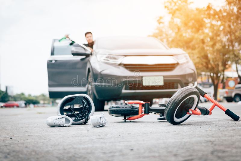 Man who is drunk driving crash child bike and open door to watch by holding a bottle of beer.  royalty free stock images