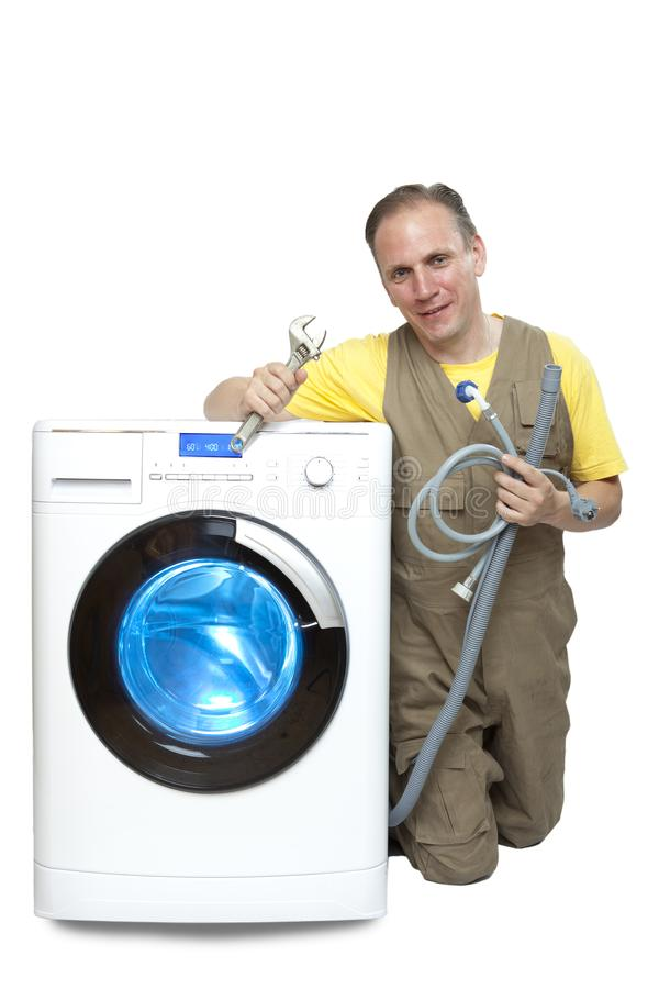 The man who has thought of repair or connection of the washing machine near the new washing machine stock image