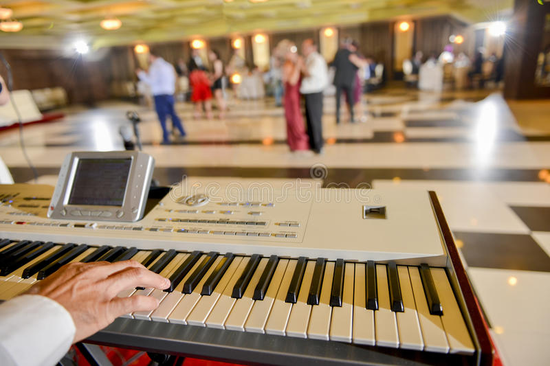Man who playing on a electronic piano in restaurant stock images