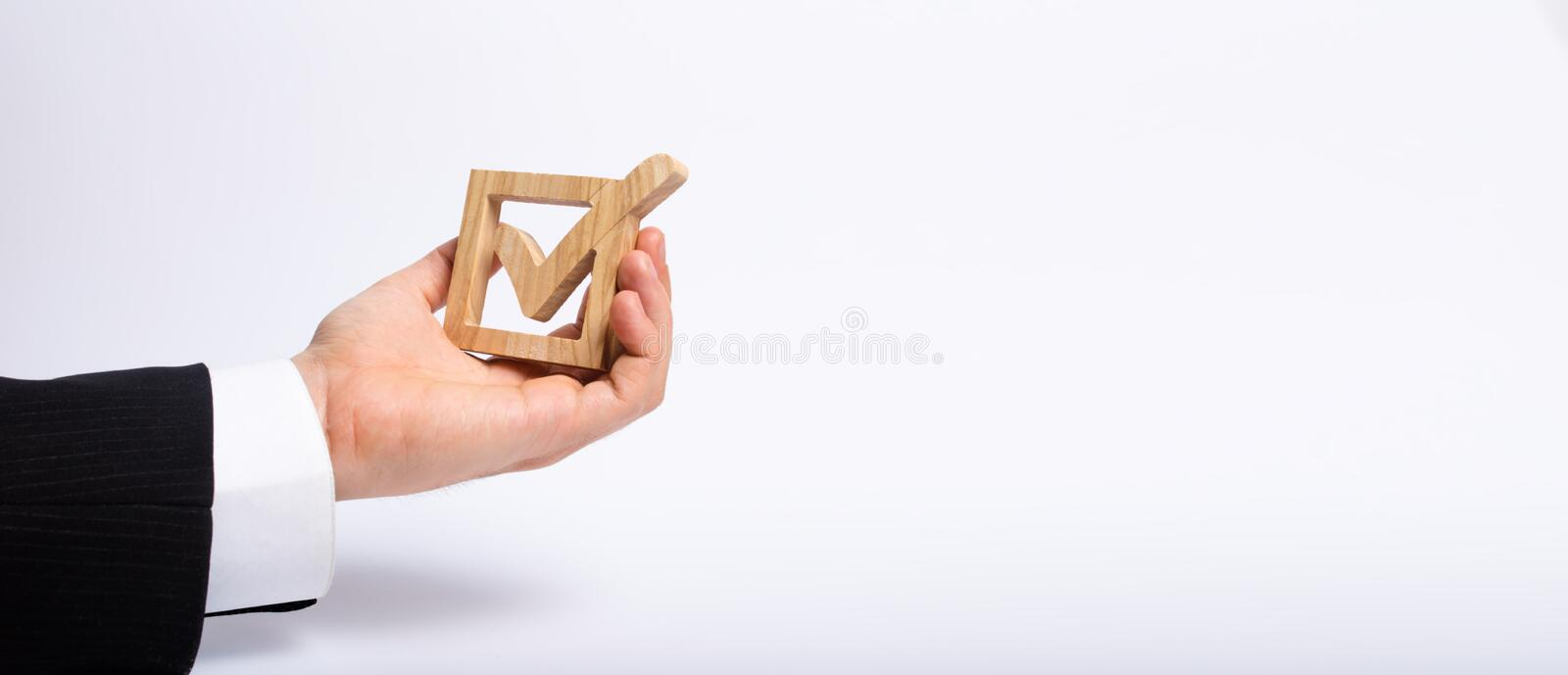 A man who is unemployed in a business suit is holding a wooden box. a tick in the box. The hand holds a wooden check box with. A tick. Concept business goals stock photo