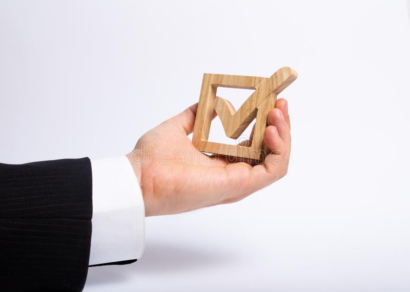 A man who is unemployed in a business suit is holding a wooden box. a tick in the box. The hand holds a wooden check box stock images