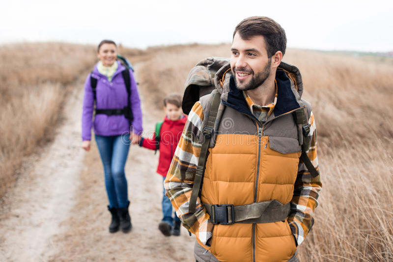 Man with wife and son backpacking. Close-up portrait of young men with wife and son backpacking in rural area at cloudy autumn day stock image