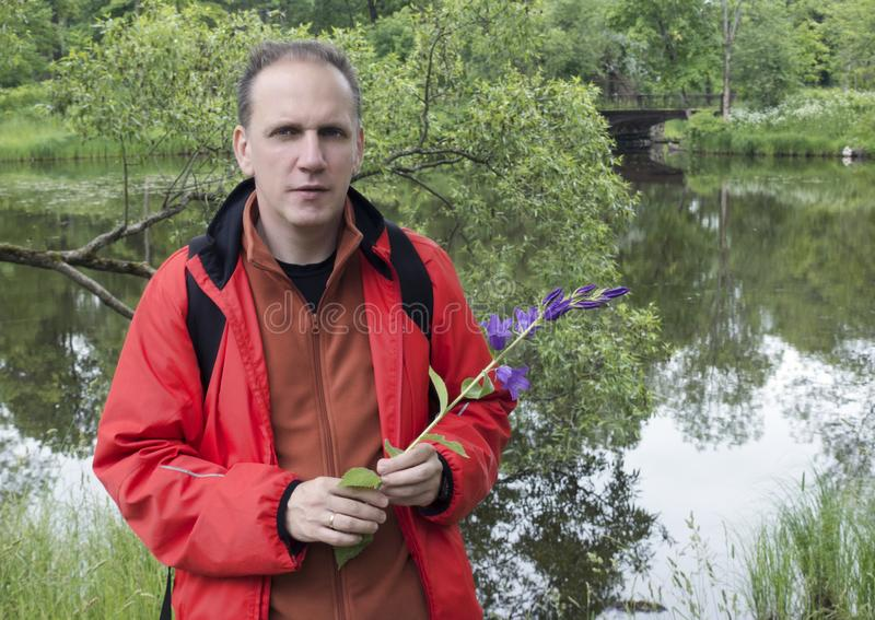 Man with wild bell flowers by the lake royalty free stock photography