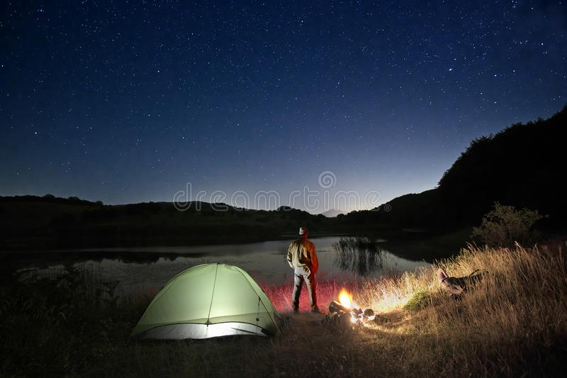 Man And Wild Camp By The Lake Under Starry Sky stock photos