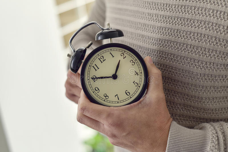 Man winding or adjusting the time of a clock stock photography