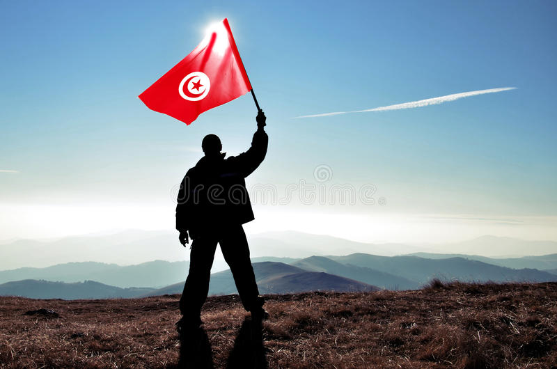 Man winner waving Tunisia flag. Successful silhouette man winner waving Tunisia flag on top of the mountain peak stock photo