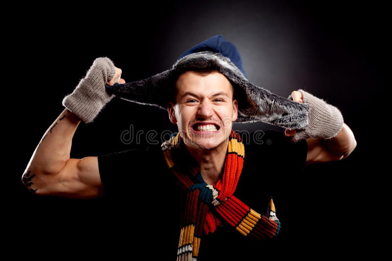 Man in winter clother pulling his furry hat royalty free stock photography