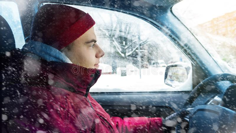 A man in winter clothes drives a car in winter. A man in winter clothes drives a car in royalty free stock photography