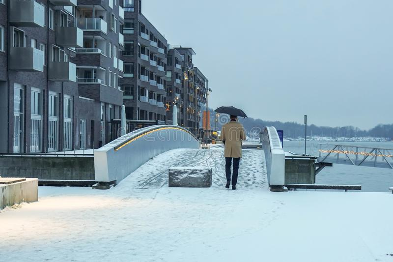Man in winter coat with umbrella in snowy day in Oslo, Norway royalty free stock images