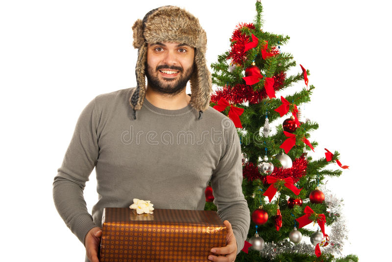 Man with winter hat. And Christmas present in front of tree royalty free stock photo