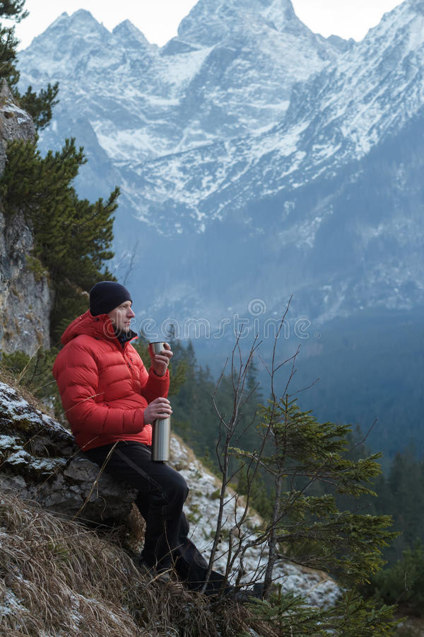 Man in winter mountains resting and drinking from vacuum flask metal cup stock photos