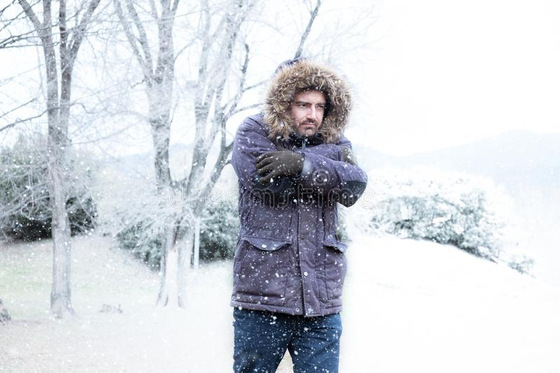 Man in winter season and snowy day. Man in cold and snowy weather storm in winter royalty free stock photography