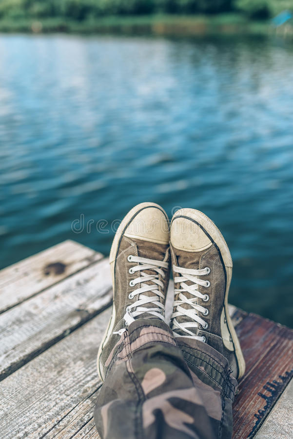 Free Man With Crossed Legs Relaxing On Riverbank Pier Stock Photos - 76072253