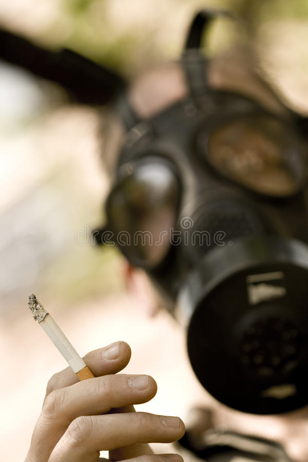 Free Man With Gasmask Holding Lit Cigarette Royalty Free Stock Photography - 10772997