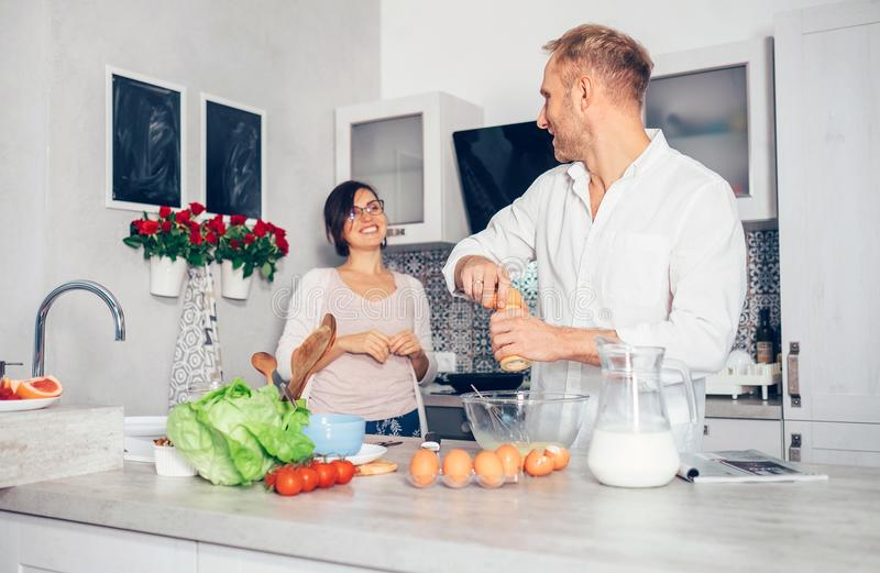 Man and woaman cooking breakfast together on kitchen stock photo