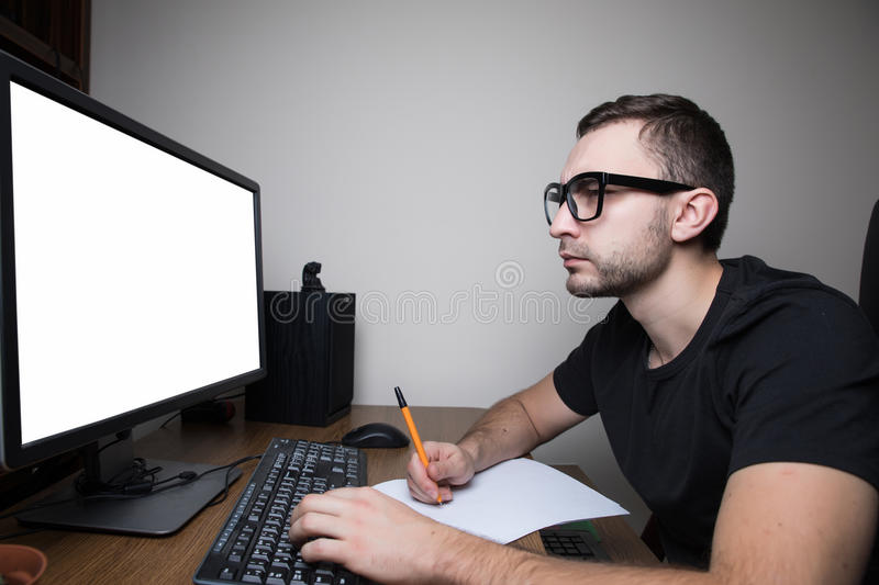 Man woking at PC on white screen monitor and make notice. On paper royalty free stock image