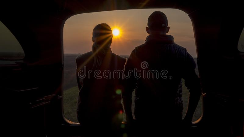 A man and a woman admire the beautiful sunset from the trunk of a car royalty free stock photography