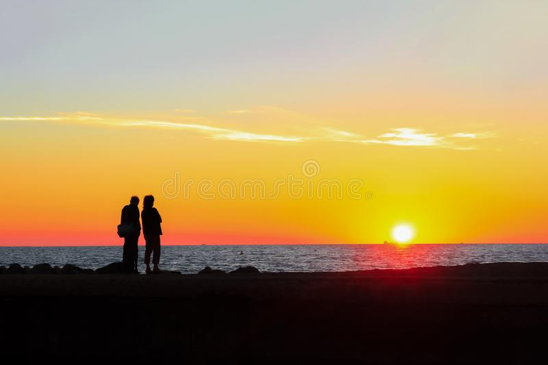 Man and woman admire the colorful sunset on the beach royalty free stock photos