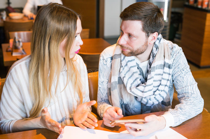 Man and woman arguing indoors. Man and women arguing about home finances royalty free stock image
