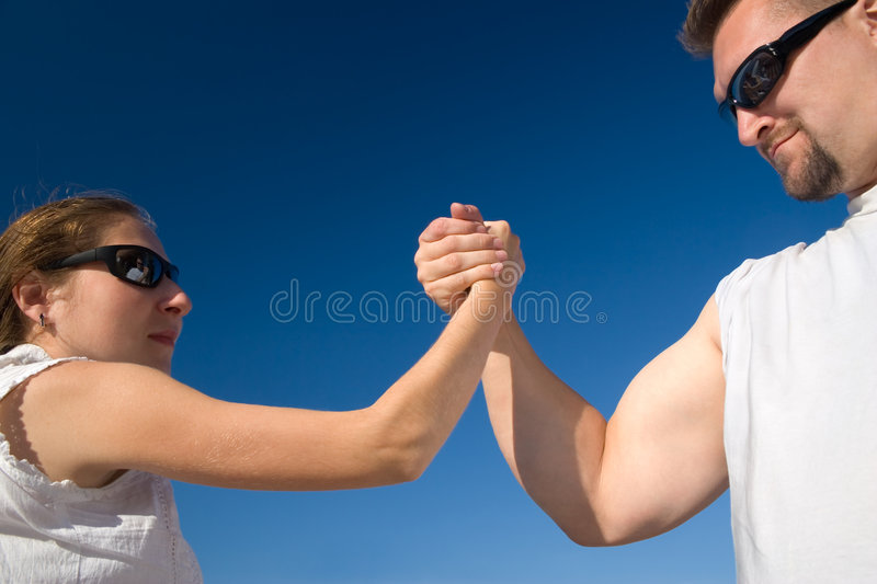 Man and Woman Arm Wrestling Outdoors. Man and Woman arm wrestling. They are competing outside on a sunny day royalty free stock images
