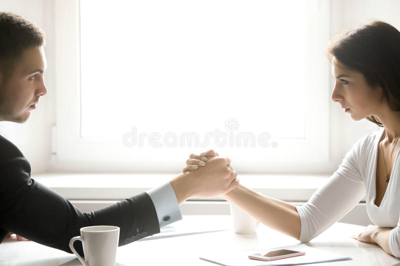 Man and woman armwrestling. Side view portrait of men and women armwrestling, exerting pressure on each other, looking eyes in eyes, struggling for leadership royalty free stock images