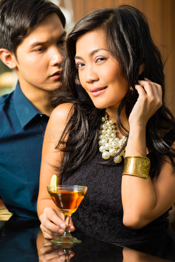 Man and woman in asia at bar with cocktails stock photos