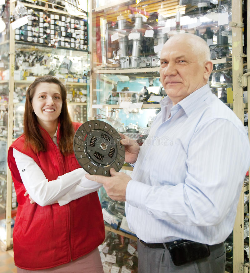 Man and woman in auto parts store royalty free stock photography