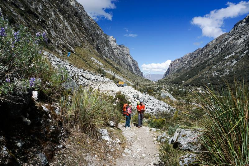 Man and woman backpacker in the Andes of Peru return from the remote wilderness back to civilization at a modern road head. A backpacker and mountain climber royalty free stock photo