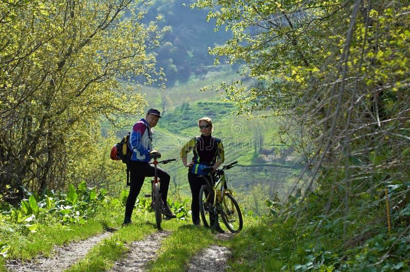Man and woman on bikes royalty free stock photos