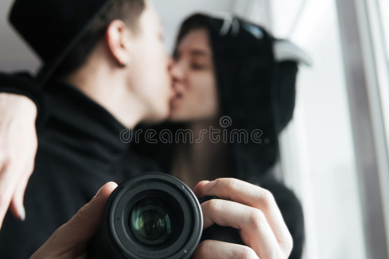 Man and woman in black clothes kissing. Man and women in black clothes photographed themselves in the mirror royalty free stock image