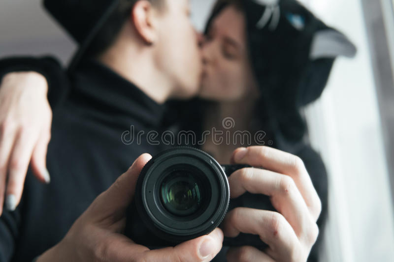Man and woman in black clothes kissing. Man and women in black clothes photographed themselves in the mirror royalty free stock photo