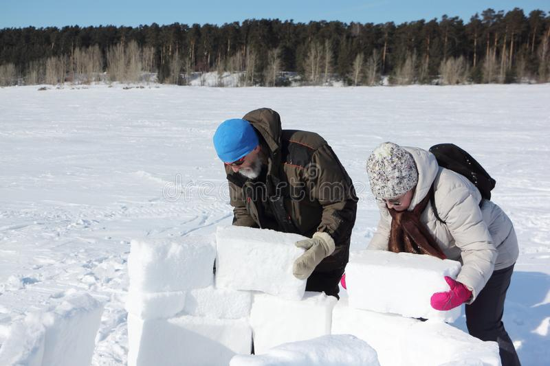 Man and woman building an igloo in snowy glade, Novosibirsk, Russia stock image