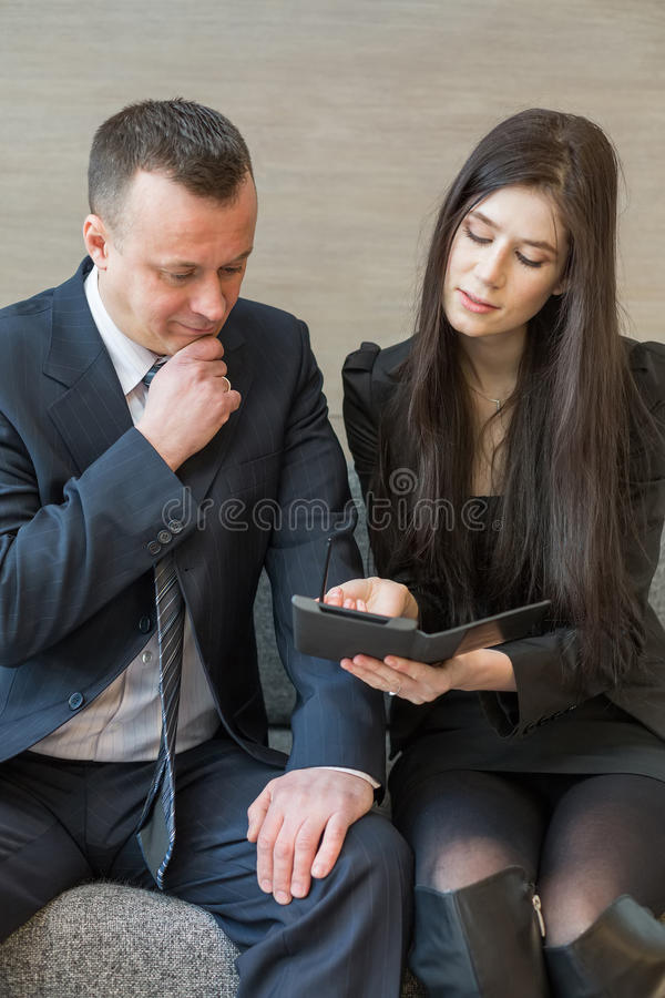 Man and woman in business suits sitting on the sofa royalty free stock photos