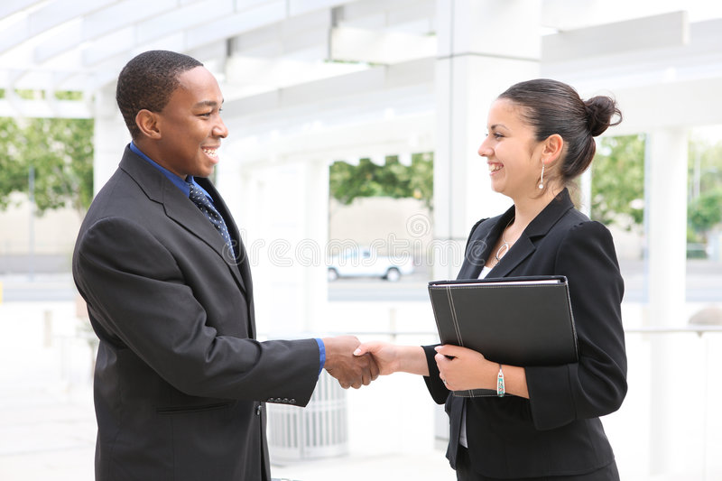 Man and Woman Business Team Handshake. An attractive, diverse, business team man and woman handshake royalty free stock photography