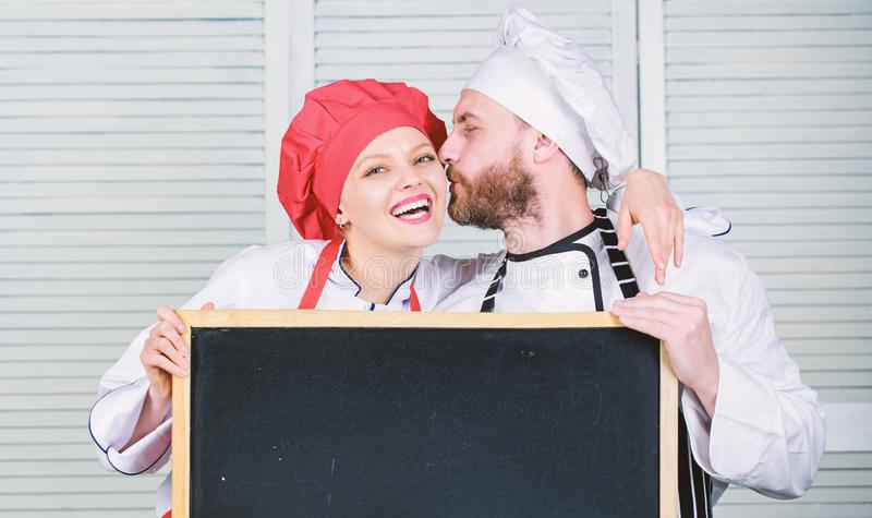 Man and woman chef cooking food together. Couple with blackboard for advertisement. Lovely family at kitchen. Family stock photography