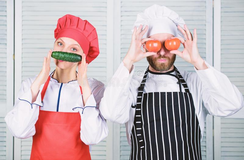 Man and woman chef hold vegetables having fun. Couple play with ingredients for vegan dish. Cooking vegan meal. Cooking royalty free stock photography