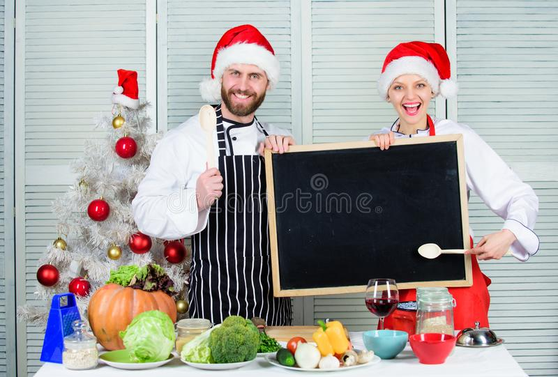 Man and woman chef santa hat near christmas tree hold blackboard copy space. Cooking christmas meal. Family traditional royalty free stock photo