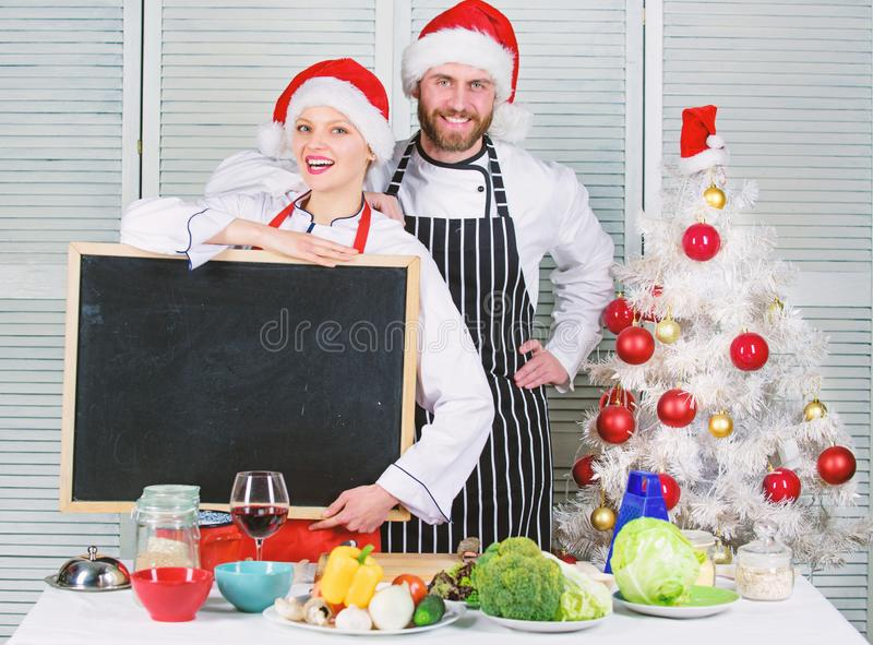 Man and woman chef santa hat near christmas tree hold blackboard copy space. Christmas recipe concept. Family royalty free stock photography