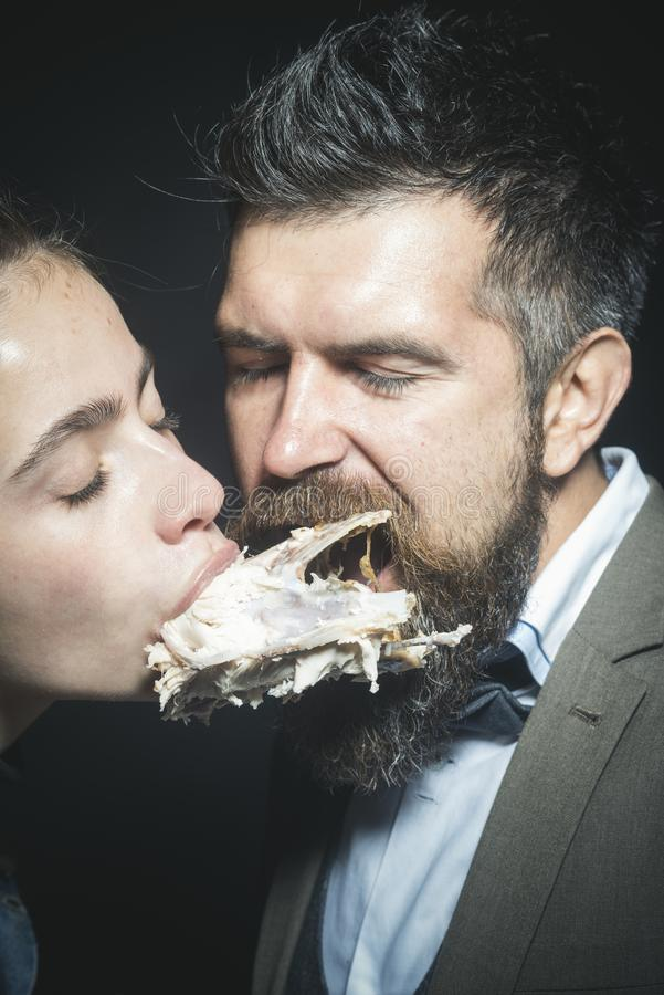 Man and woman with chickens skeleton in mouths, black background. stock photo