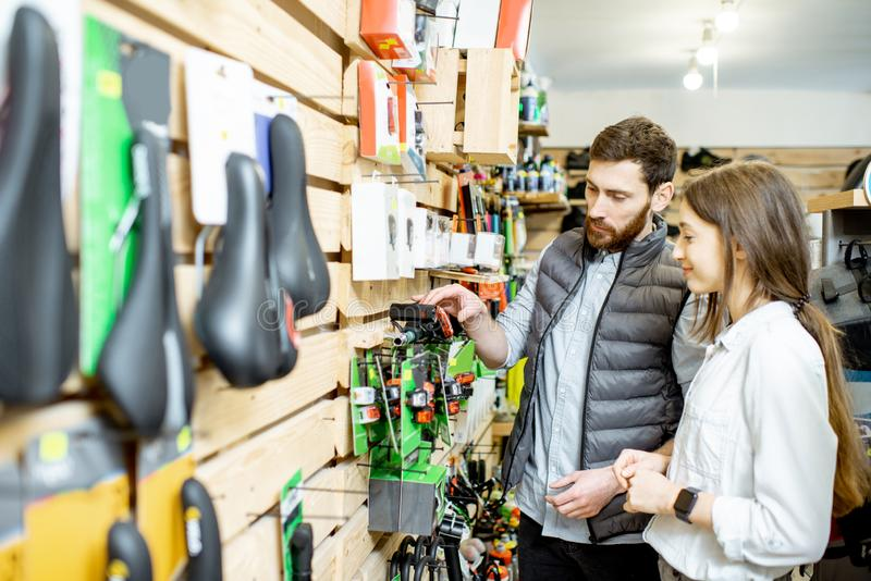 Man and woman choosing bicycle parts in the shop stock photo
