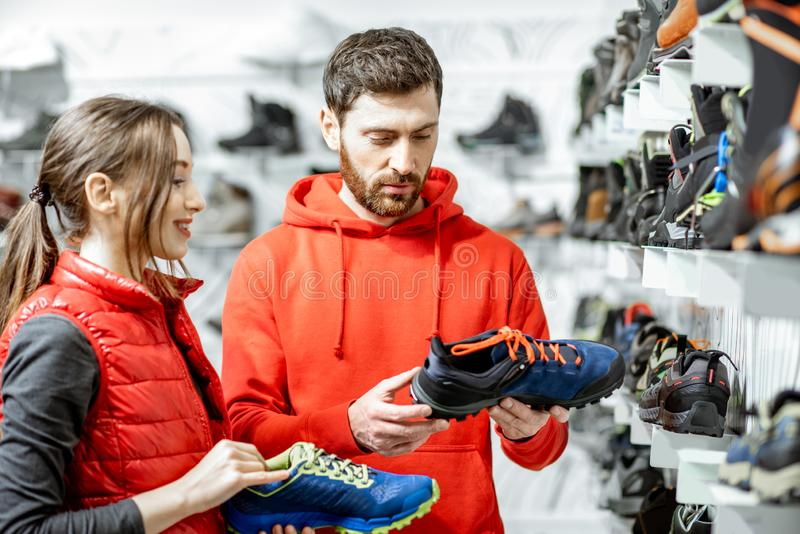 Man and woman choosing shoes in the shop royalty free stock image
