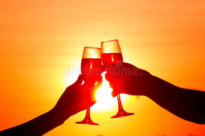 Man and woman clanging wine glasses with champagne at sunset royalty free stock image