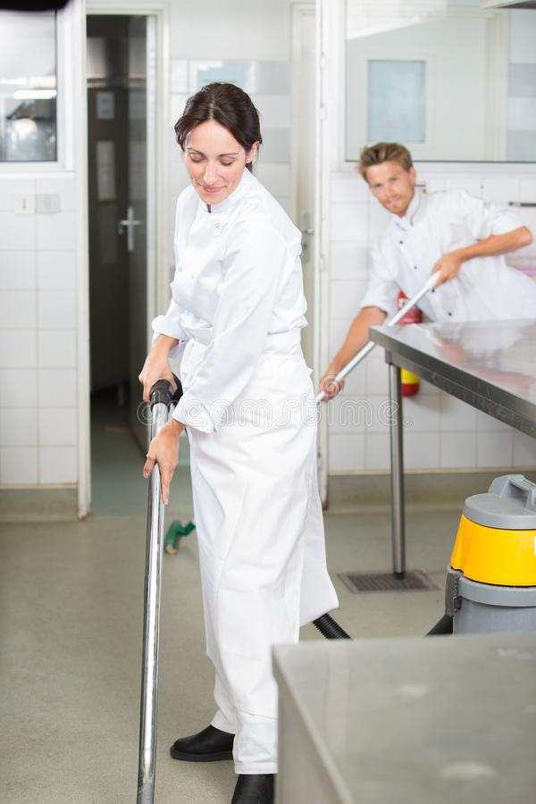 Man and woman cleaning floor in profesional kitchen royalty free stock image