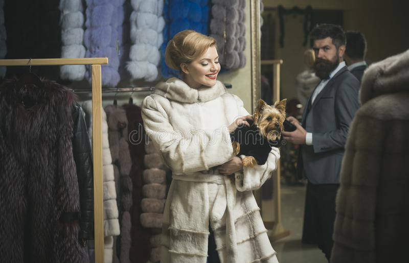 Man and woman with coats in fur shop. Man with strict face and women with coats in fur shop. Money and style concept. Woman in fur coat with dog and men in shop stock images