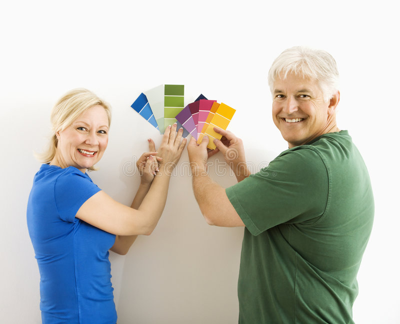 Man and woman comparing swatches. Middle-aged couple holding up and comparing paint swatches stock photography