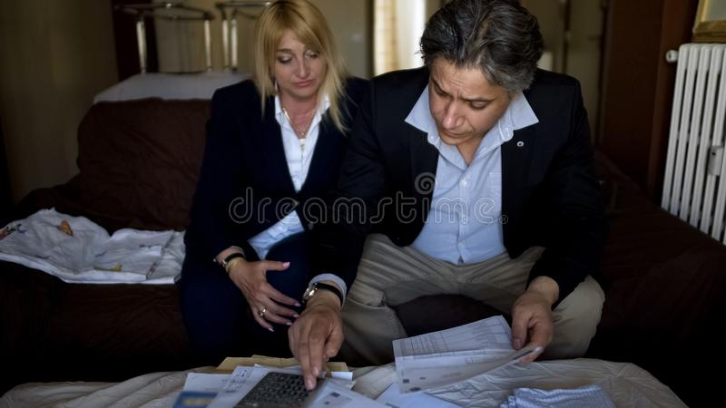 Man and woman counting expenses, checking bills for utilities, family budget royalty free stock images