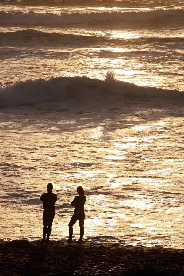 Man & woman couple on beach at sun set