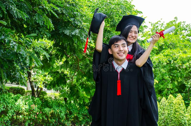 A man and woman couple dressed in black graduation gown or graduates with congratulations with graduation hats is standing, royalty free stock photo
