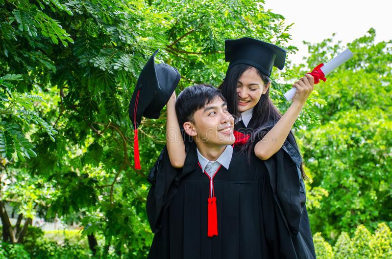 A man and woman couple dressed in black graduation gown or graduates with congratulations with graduation hats is standing, stock image