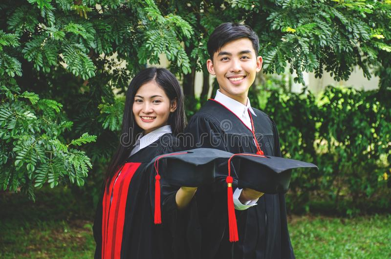 A man and woman couple dressed in black graduation gown or graduates with congratulations with graduation hats is standing stock image